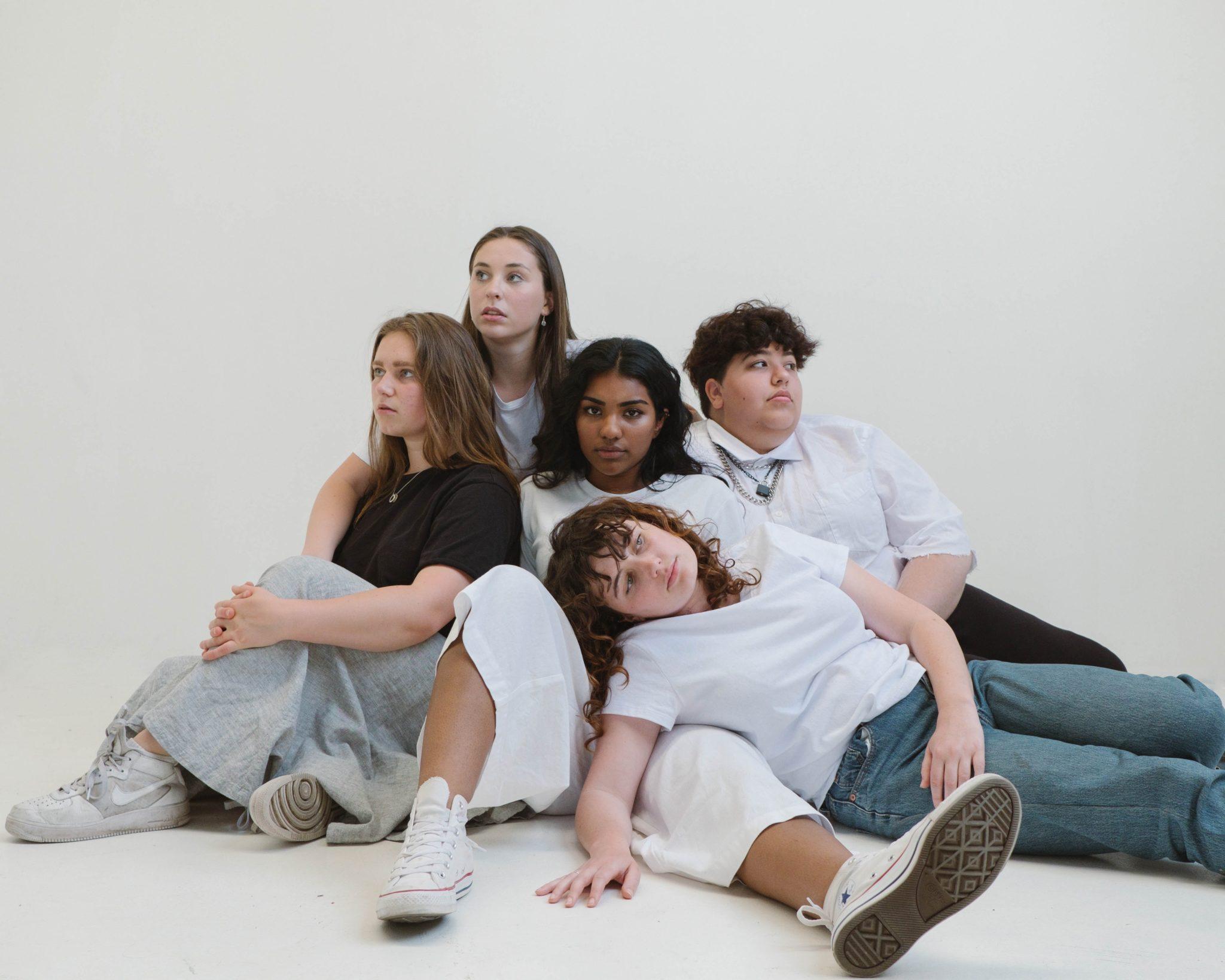 Bilde av en gruppe kvinner som ligger på gulvet. Det er til sammen fem kvinner, som støtter seg mot hverandre.