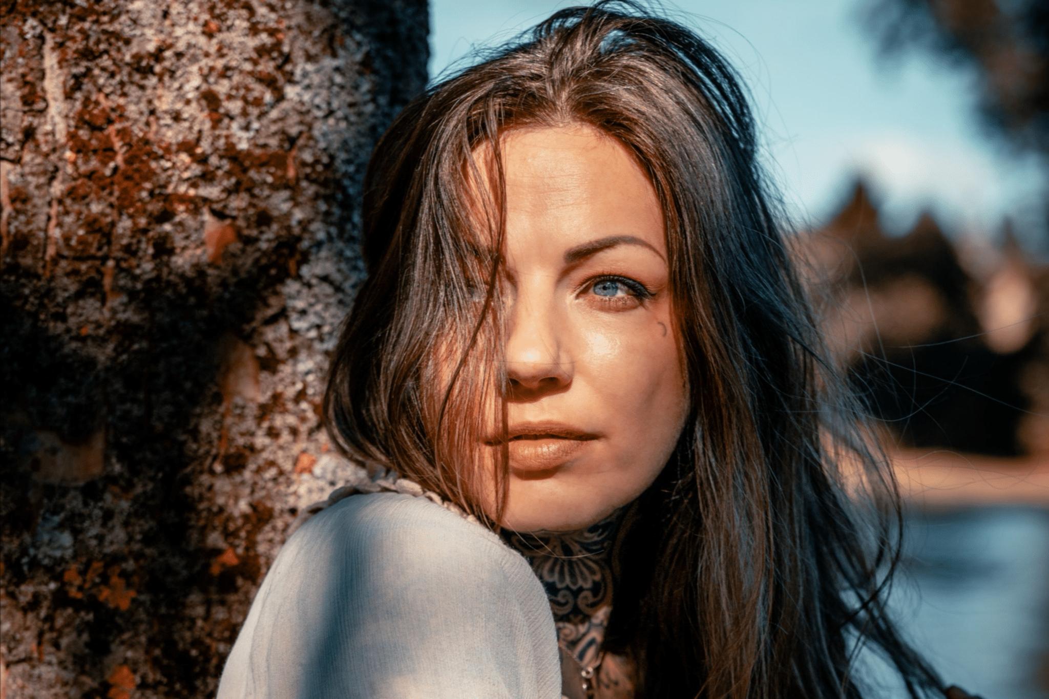 Bilde av Sally-Ann Eilertsen, en mørkhåret og lyshudet kvinne. Hun lener seg inntil et tre, og ansiktet treffes av varmt lys.