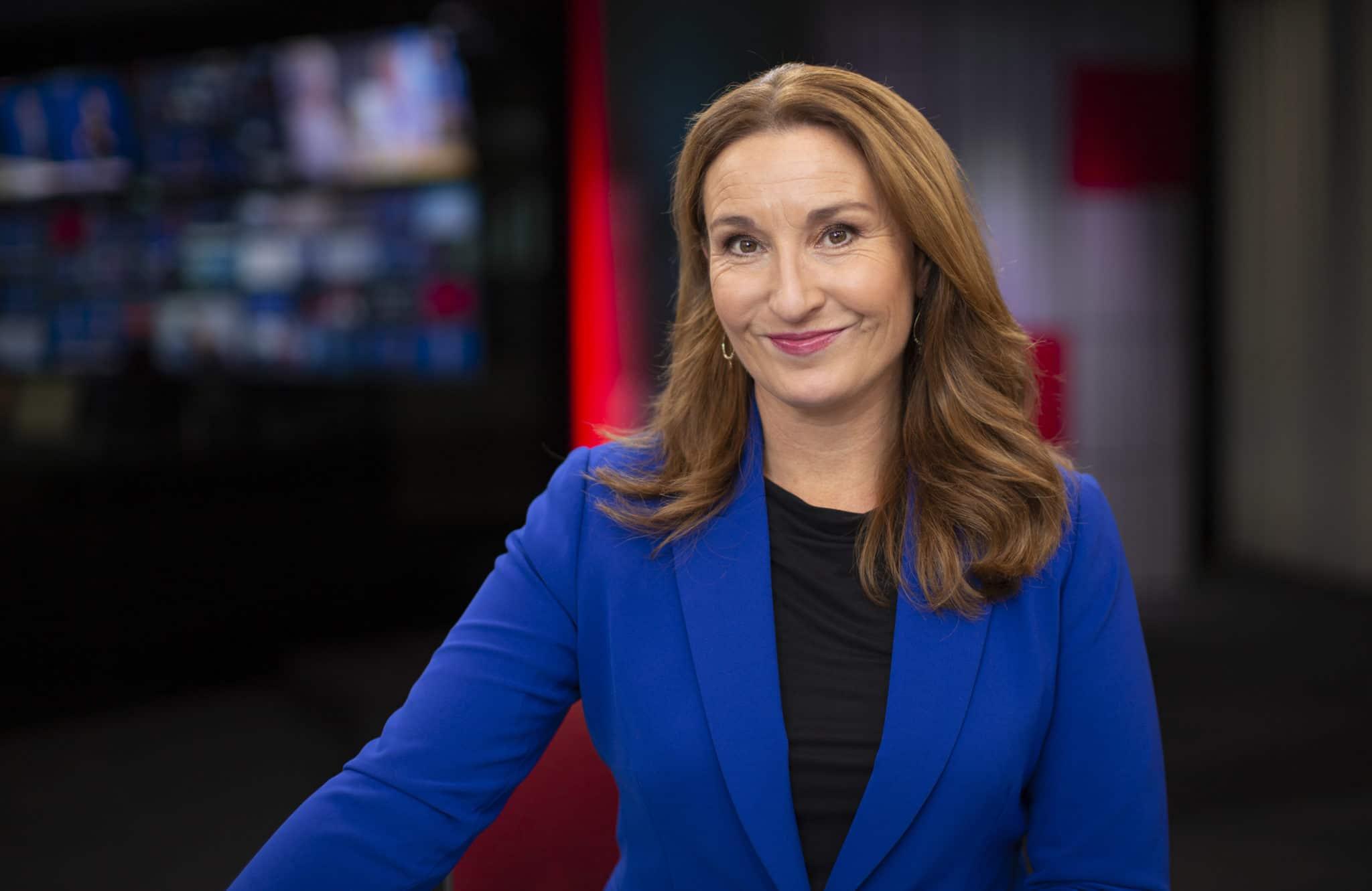 Bilde av Elin i en blå jakke, med sort topp under. Elin sitter i et TV-studio, og smiler.