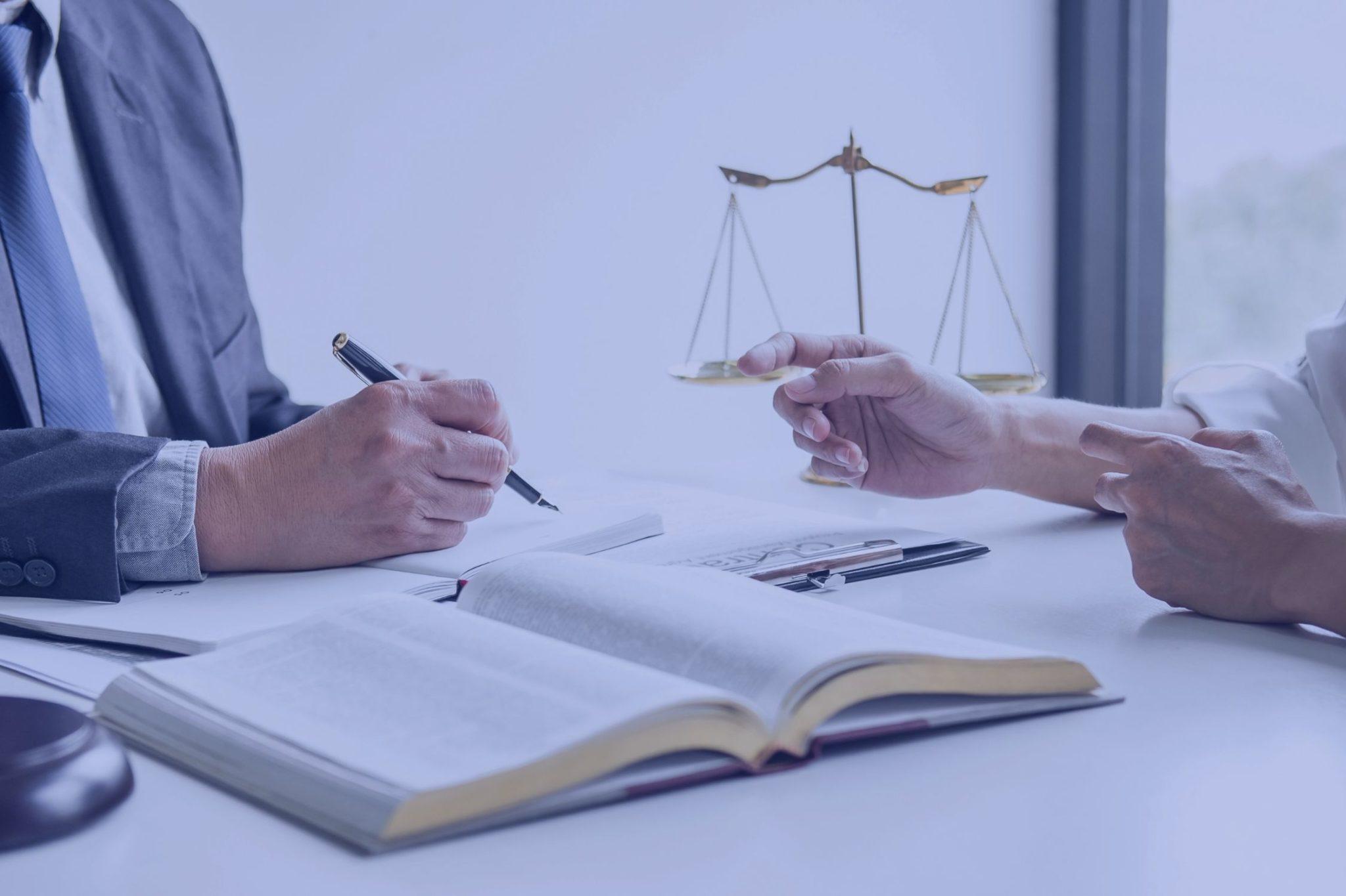 Nærbilde av hender over en lovbok