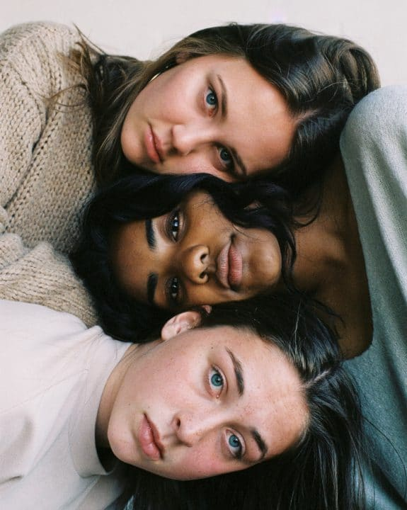 Tre unge kvinner lener hodet på hverandre